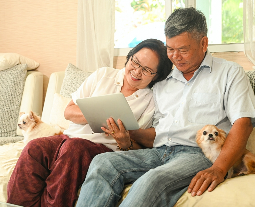 Elderly woman and an asian man sitting on a sofa are using a tablet.