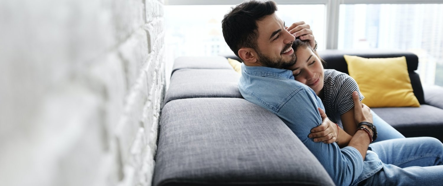 Young Couple Hugging and Kissing on Sofa